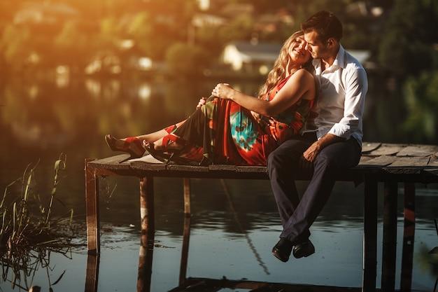 木製の港に彼女のボーイフレンドに横たわっている女性