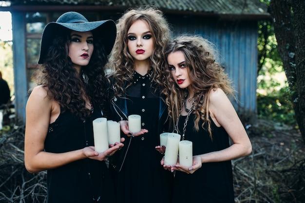 女の子は白いろうそくを保持している魔女に変装します