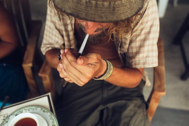 Человек, освещающий сигарету