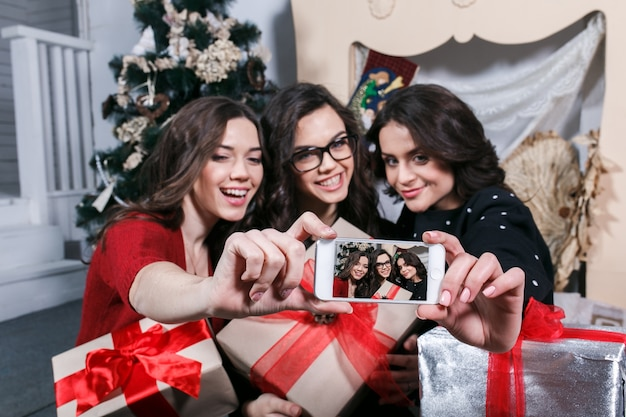 彼らの贈り物と一緒に写真を撮るの友達を笑顔