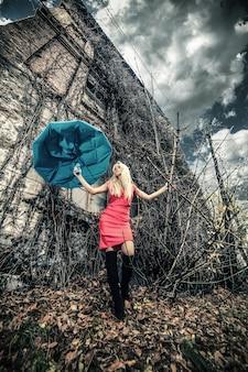 捨てられた場所に傘を持つ女性
