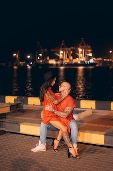 若い男と夜港の背景の美しい少女