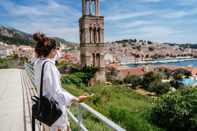 Молодая красивая женщина на балконе с видом на маленький городок в хорватии