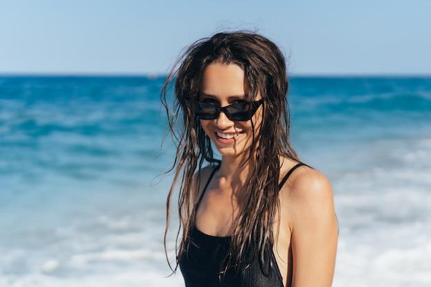 Красивая молодая женщина в черном мокром купальнике
