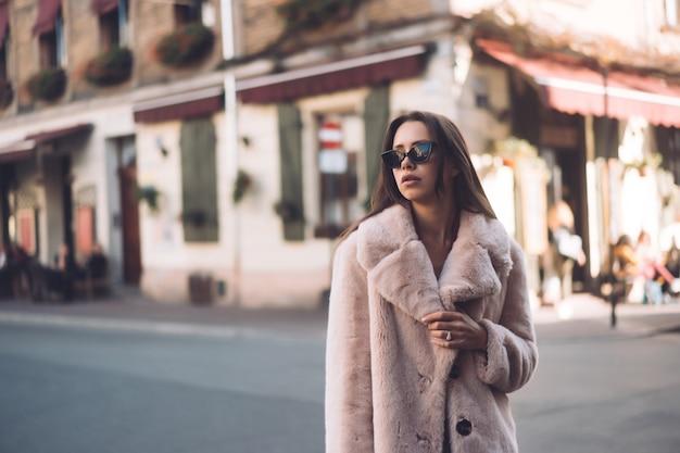 ピンクのコートを歩いて若い美しいスタイリッシュな女性