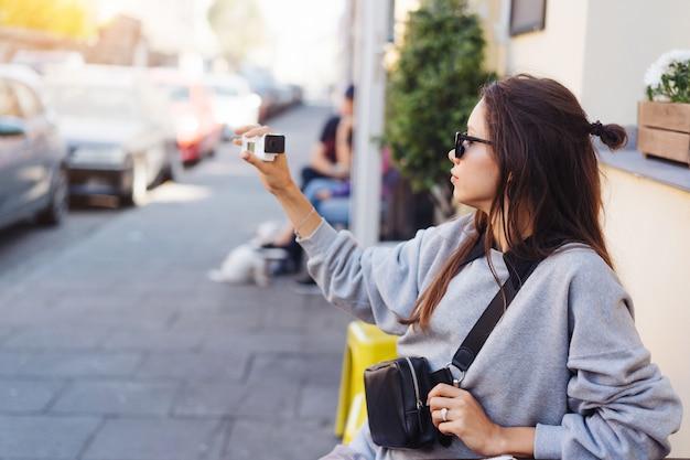 カメラでポーズかわいい、若い女性のブロガー。