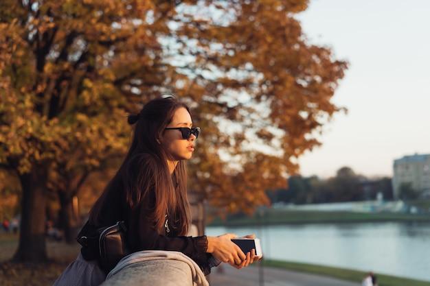 公園で屋外のスマートフォンを使用して魅力的な女性