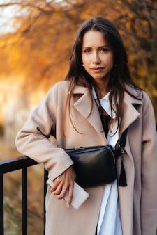秋の公園に立っている美しいエレガントな女性