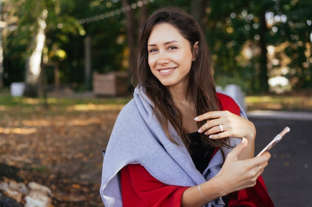 Портретное фото молодой девушки со смартфоном