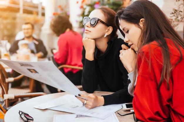 Две красивые стильные женщины сидят за столом в уличном кафе