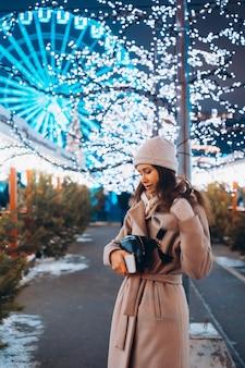 Девушка позирует на фоне украшенных деревьев