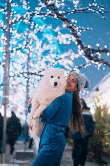 女性が犬を腕に抱えています。