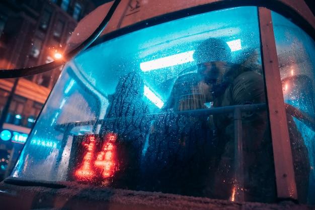 男と少女は曇ったガラスの後ろの路面電車でキスします