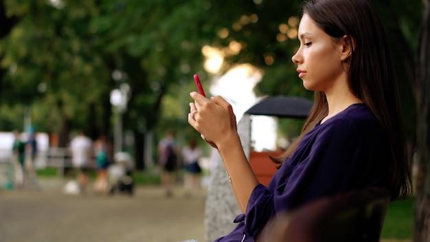 女性はベンチに座って、スマートフォンを使用しています。ビューを閉じる
