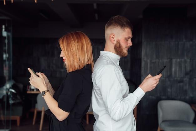 若い人たちは、スマートフォンを手にした背中合わせに立ちます。