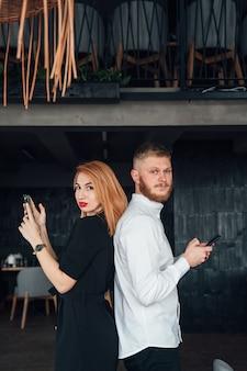 Молодые люди стоят спиной друг к другу со смартфонами в руках.