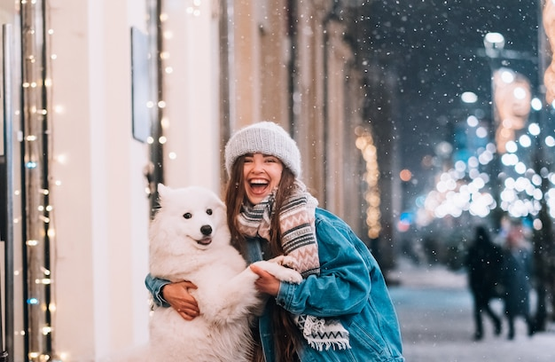 女性が夜の街で犬を抱いています。