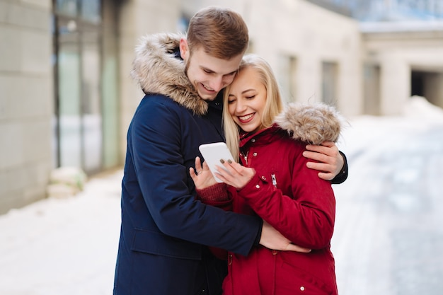 Девушка держит телефон в руке, и они смотрят на смартфон.