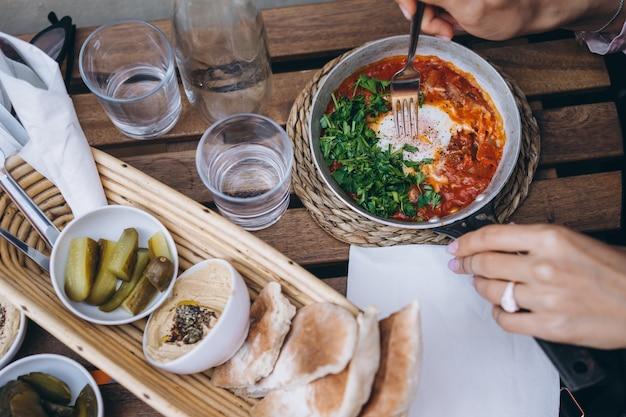 シャクシュカ、テーブルの上のトマトソースの目玉焼き