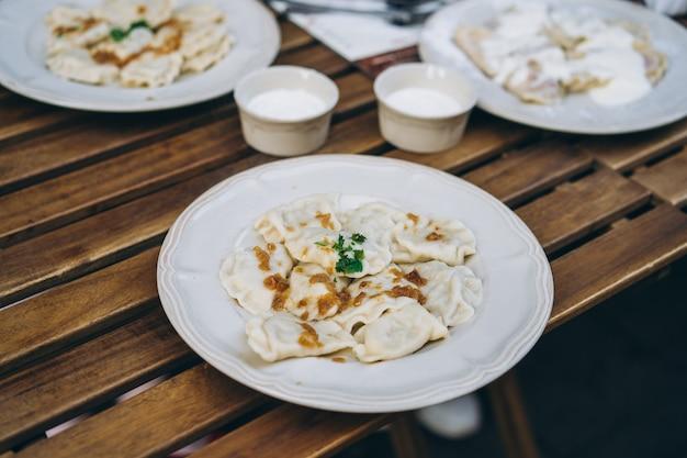 Пельмени с беконом и зеленью на тарелке