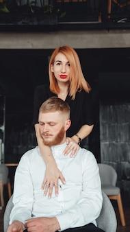 若い女性と彼氏が屋内でカメラに向かってポーズをとっている。
