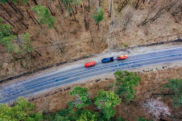 Несколько автомобилей с байдарками на крыше едут по дороге среди деревьев