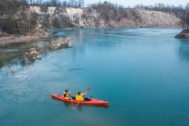 Два спортивных человека плавает на красной лодке в реке