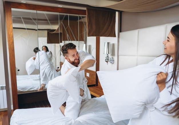 陽気なカップルが自宅で大きな枕と戦う寝室で楽しい時を過す
