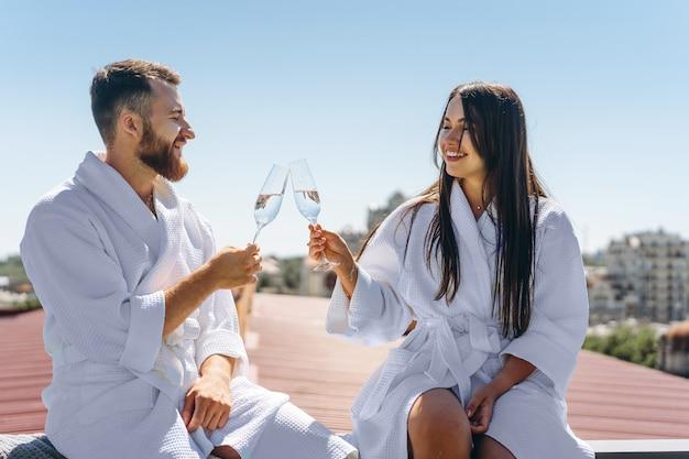 Флирт пара с игристым вином на крыше