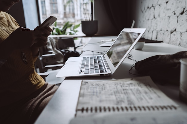 Молодая женщина, сидя на офисном столе с ноутбуком.
