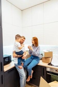 若い家族が新しい家で箱を開梱