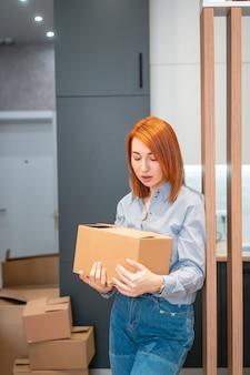Молодая женщина переезжает в новую квартиру с картонными коробками
