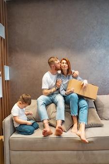 ソファの上に座って一緒に箱を開梱する子供と若い幸せな家族