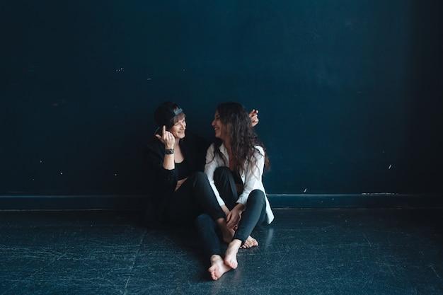 Красивые девушки сидят у стены и позируют