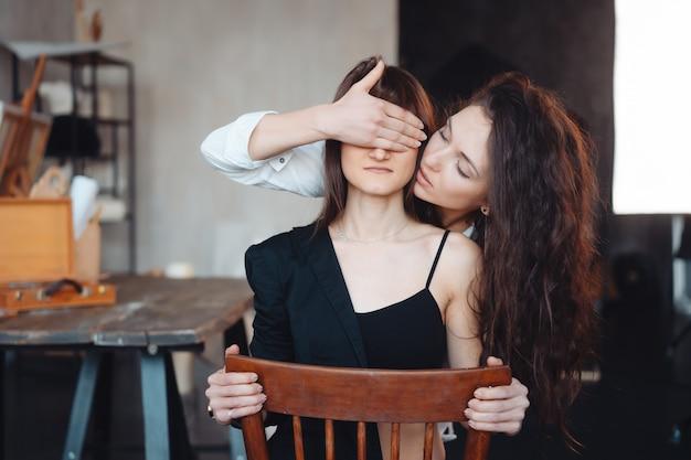 Девушка держит за руку и закрыть глаза своей подруги