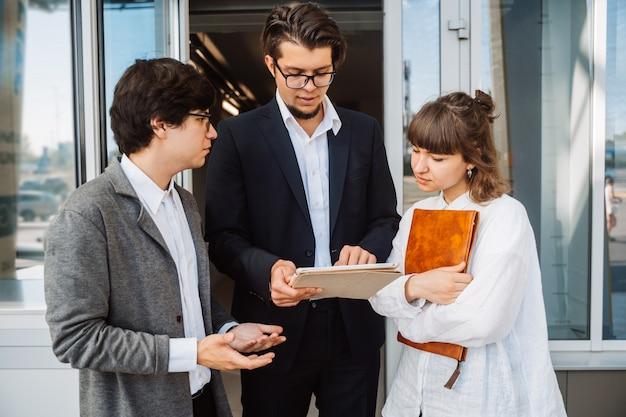 Бизнес команда двух мужчин и женщин, работающих вместе снаружи.