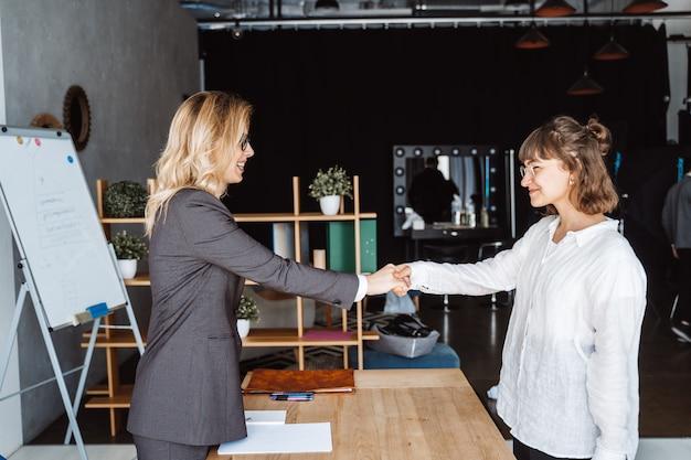 Две деловые женщины пожимают друг другу руки в офисе