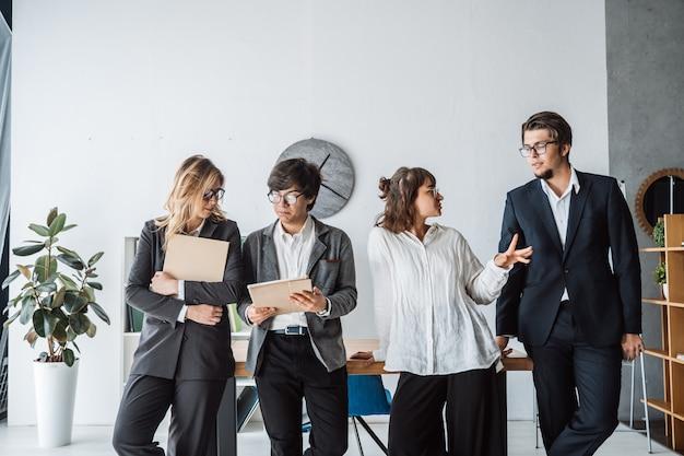 議論するオフィスに立っているビジネス人々