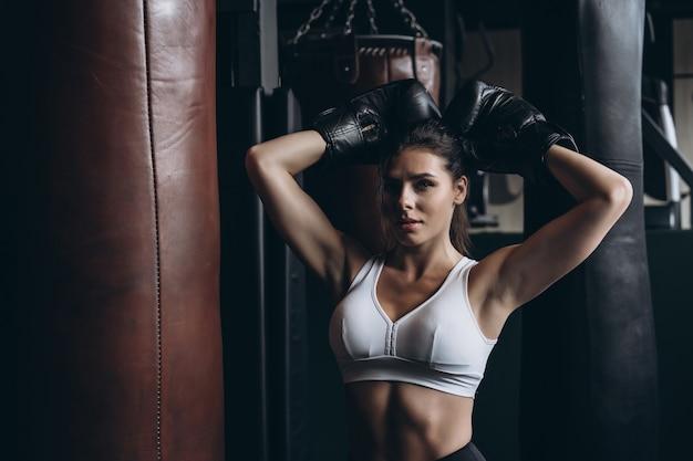 Женщина бокса представляя с грушей, на темноте. сильная и независимая концепция женщины