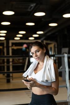 Девушка текстовых сообщений во время перерыва в тренажерном зале. читает сообщение