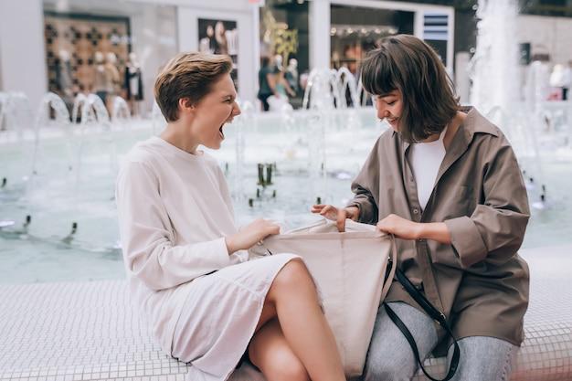 Две девушки развлекаются в торговом центре, у фонтана