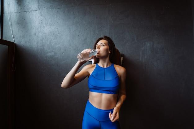 女性がカメラでポーズに合います。女の子はボトルから水を飲みます。現代のスポーツの美しさ。