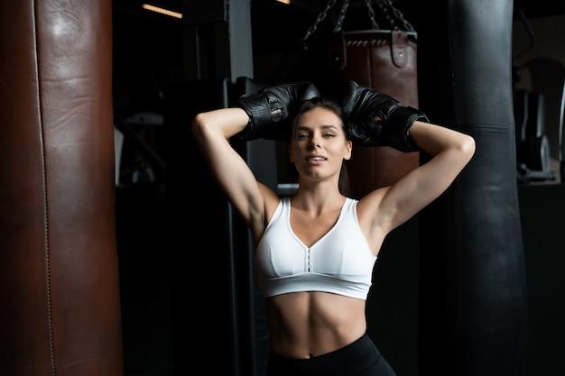 ボクシング女性がパンチングバッグ、暗闇の中でポーズします。強くて独立した女性の概念