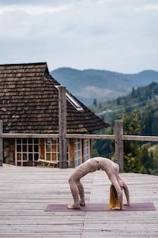 女性は朝、新鮮な空気のあるテラスでヨガを練習しています。