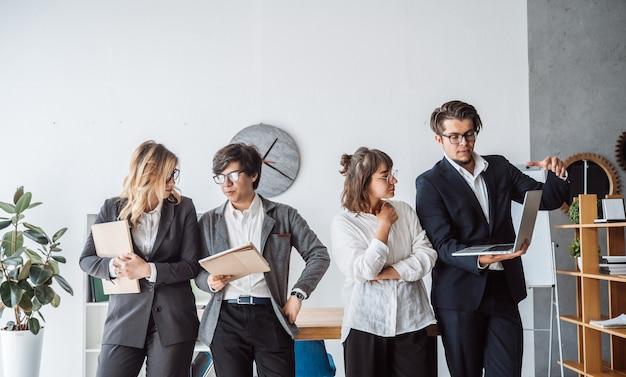 事務所に立っているビジネス人々が話し合う