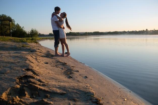 湖の背景と抱き合うカップル