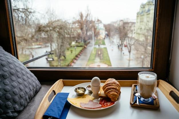 窓際の木製テーブルで朝食します。