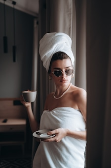 Женщина, завернутая в полотенце, пьет кофе