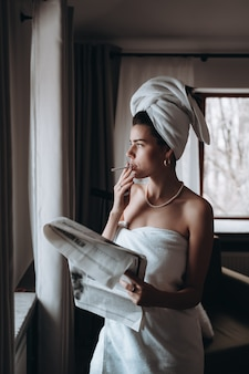 Красивая молодая женщина в полотенце курит сигарету и читает газету