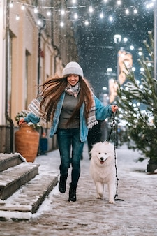 Женщина идет с белой собакой